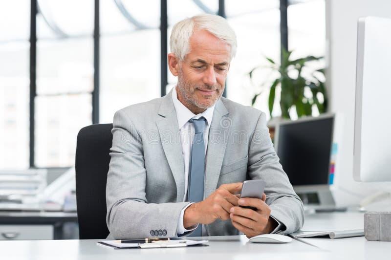 Hombre de negocios mayor que manda un SMS con el teléfono móvil imagen de archivo libre de regalías