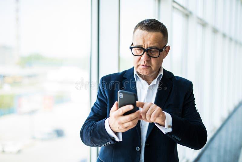 Hombre de negocios mayor que manda un SMS usando el teléfono móvil en oficina imagenes de archivo