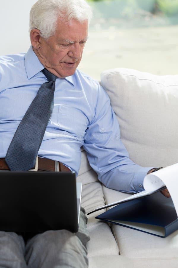 Hombre de negocios mayor que mira notas fotografía de archivo libre de regalías
