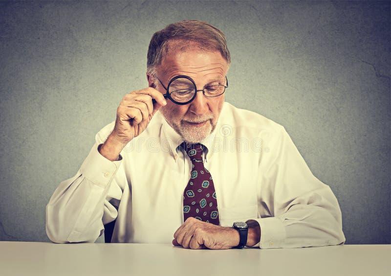 Hombre de negocios mayor que mira a través de una lupa que se sienta el escritorio de oficina foto de archivo