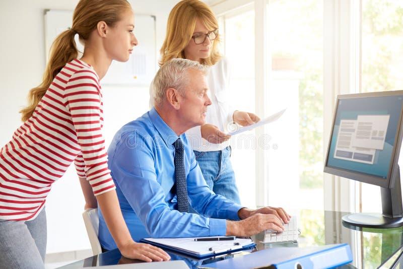 Hombre de negocios mayor que se sienta delante del ordenador con su equipo Trabajo en equipo imágenes de archivo libres de regalías