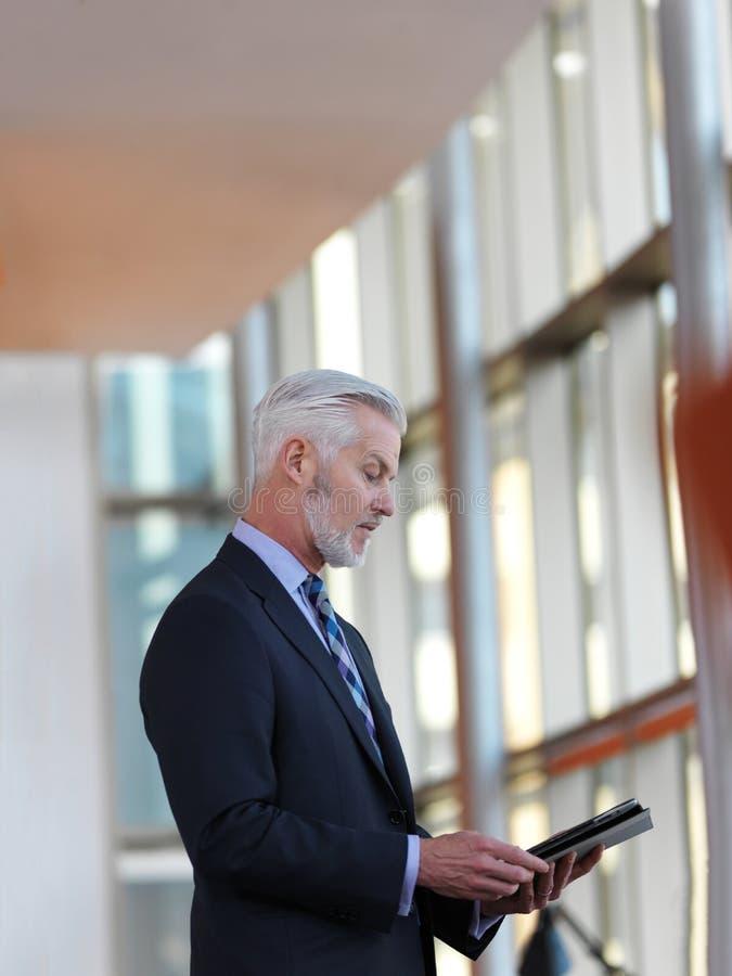 Hombre de negocios mayor que trabaja en la tableta fotos de archivo