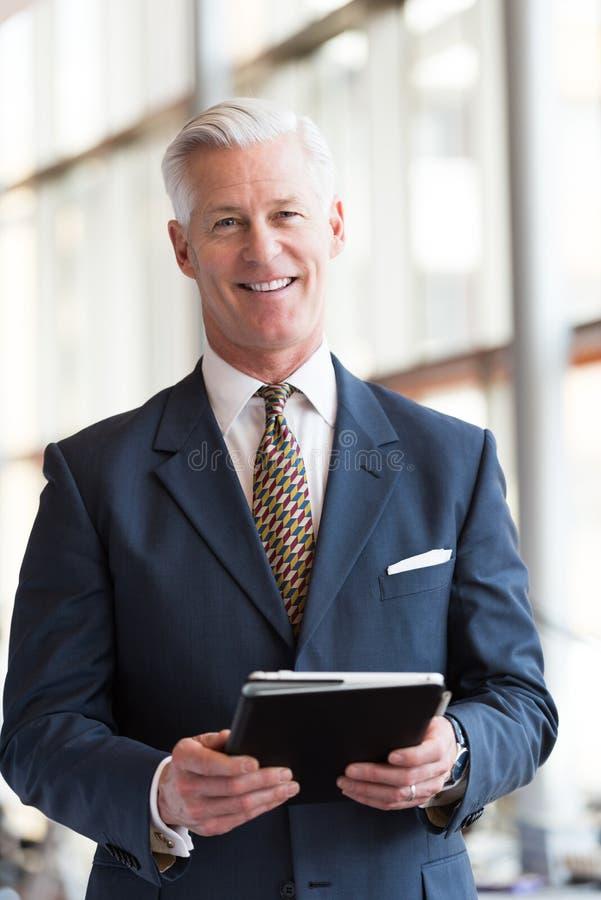 Hombre de negocios mayor que trabaja en la tableta fotografía de archivo libre de regalías