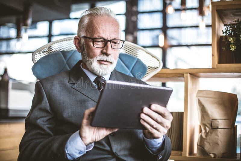 Hombre de negocios mayor que trabaja en la tableta digital Cierre para arriba imagen de archivo
