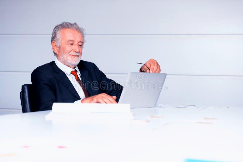 Hombre de negocios mayor que trabaja en oficina imagen de archivo