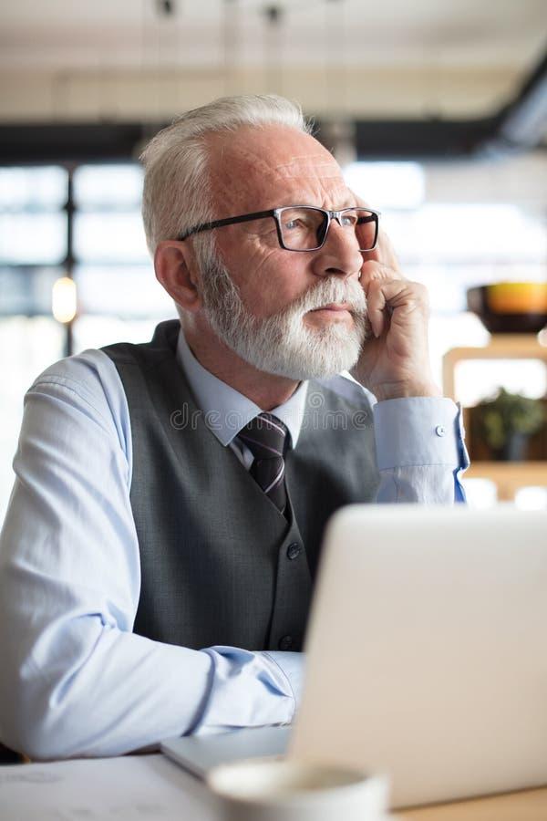 Hombre de negocios mayor que trabaja en su oficina Ciérrese encima de imagen imagenes de archivo