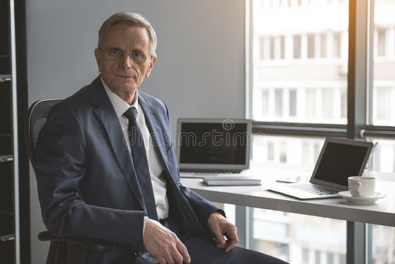 Hombre de negocios mayor sereno que trabaja en oficina fotos de archivo