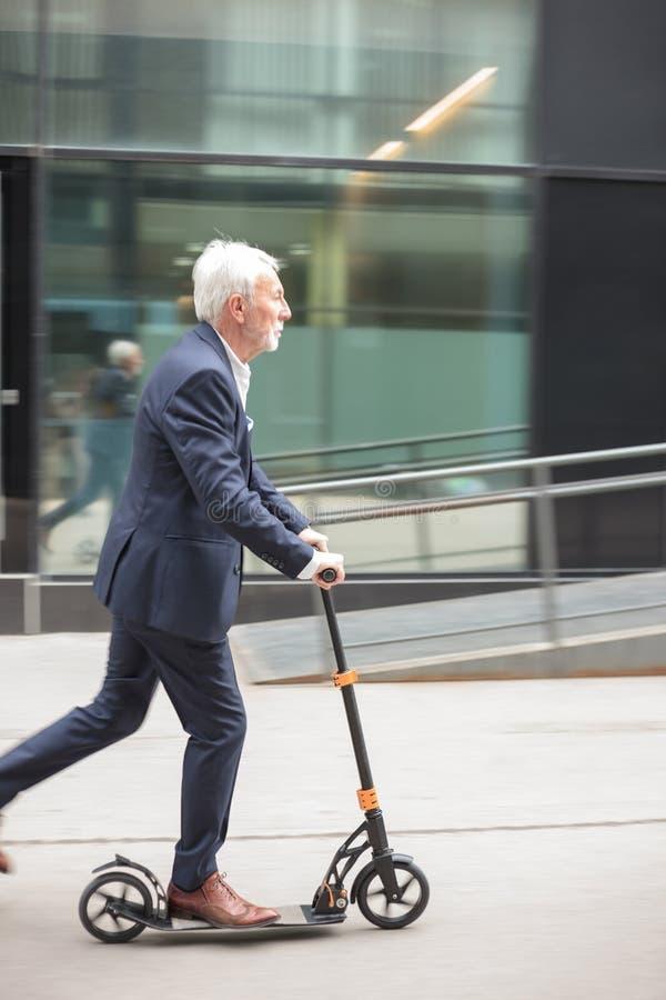 Hombre de negocios mayor serio que conmuta para trabajar en una vespa del empuje imágenes de archivo libres de regalías
