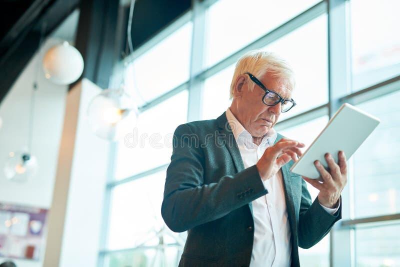 Hombre de negocios mayor usando la tableta imagenes de archivo