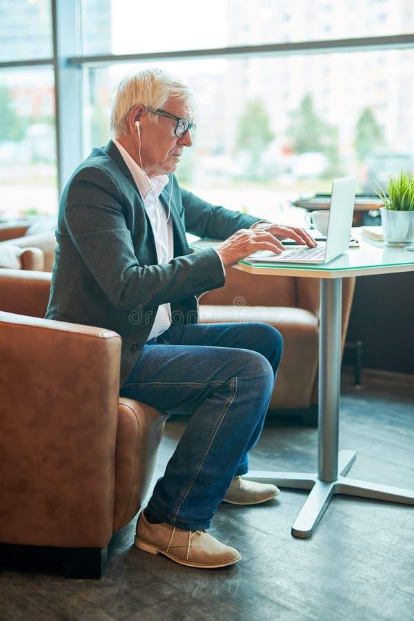 Hombre de negocios mayor Using Internet en café imágenes de archivo libres de regalías
