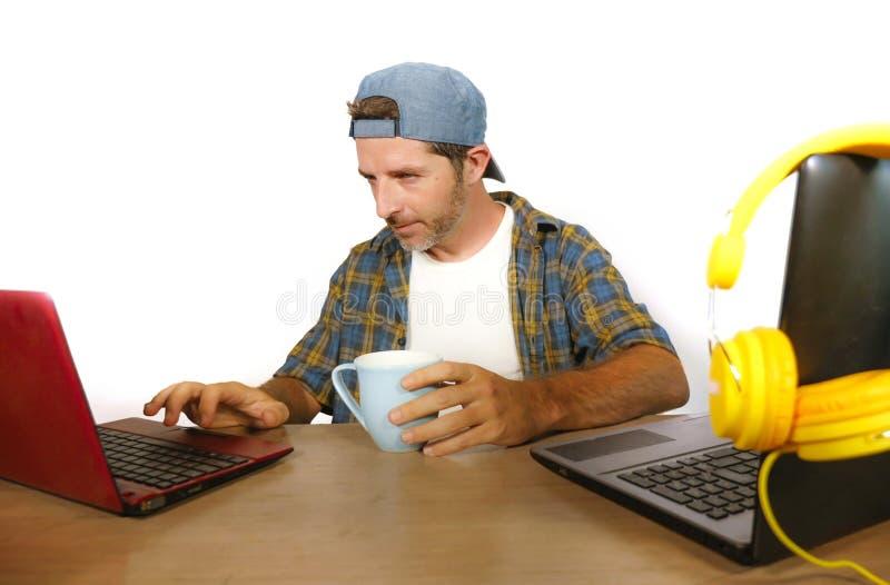 Hombre de negocios milenario feliz y atractivo joven que trabaja con el ordenador portátil como blogger de Internet y friki de la imagenes de archivo