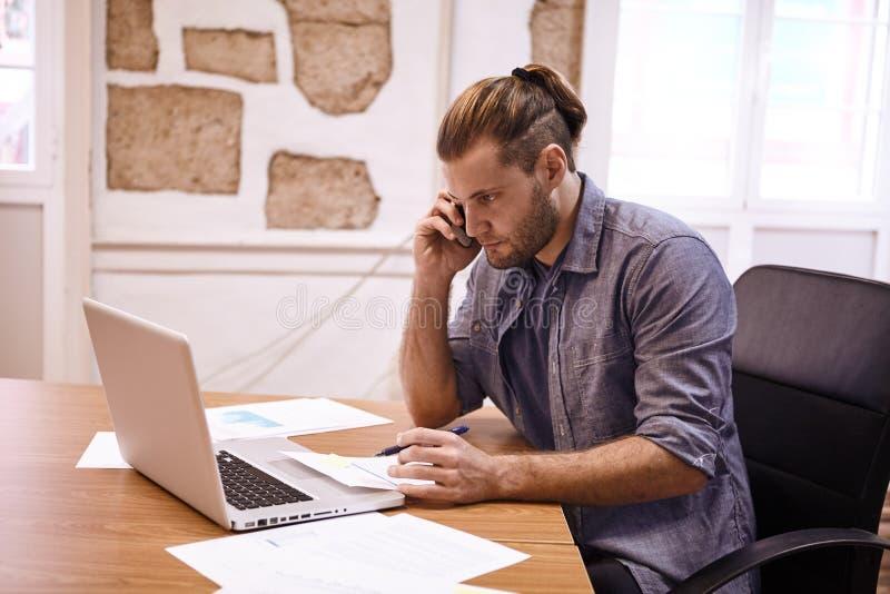 Hombre de negocios millenial joven en su teléfono imagen de archivo