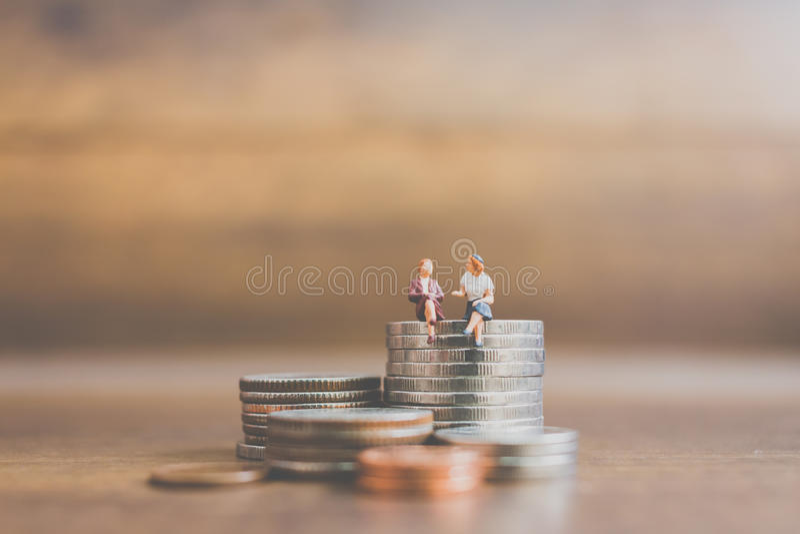 Hombre de negocios miniatura de la gente en monedas foto de archivo libre de regalías