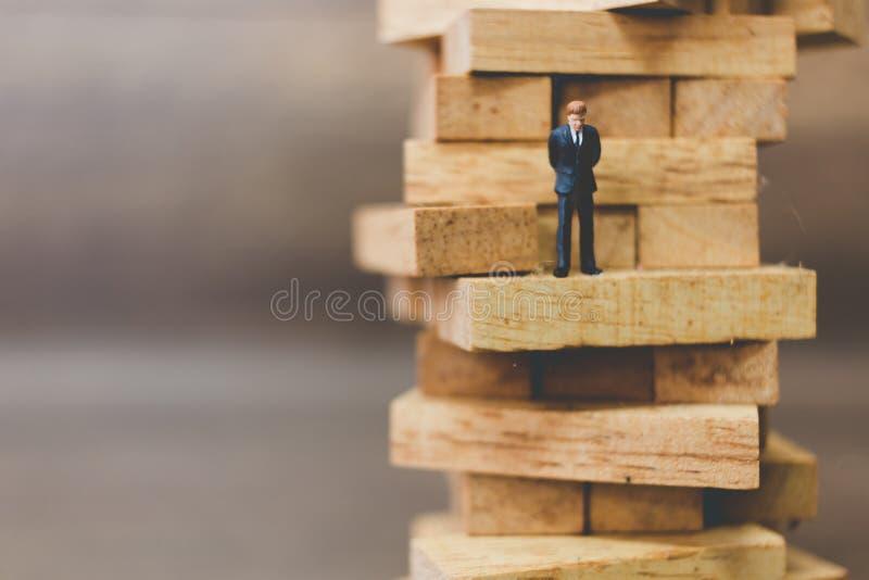 Hombre de negocios miniatura que se coloca en el bloque de madera foto de archivo libre de regalías