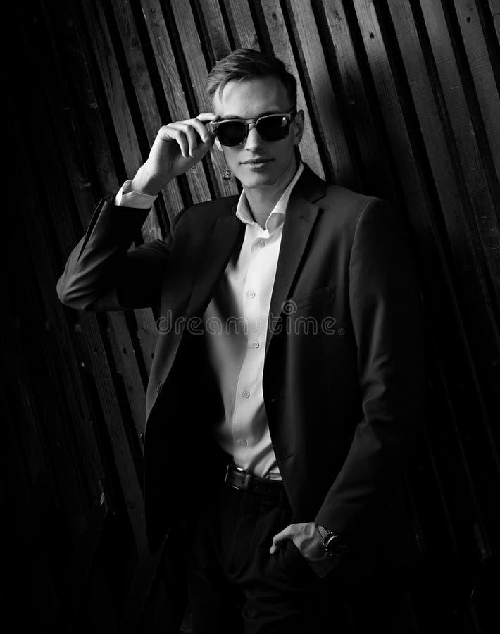 Hombre de negocios de moda en el traje que presenta en lentes de moda en blac fotografía de archivo