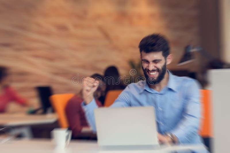 Hombre de negocios moderno caucásico barbudo joven que se sienta en una oficina de lanzamiento foto de archivo
