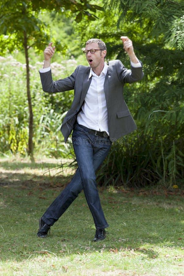 Hombre de negocios moderno de la diversión que disfruta de la promoción del trabajo en parque verde fotografía de archivo libre de regalías