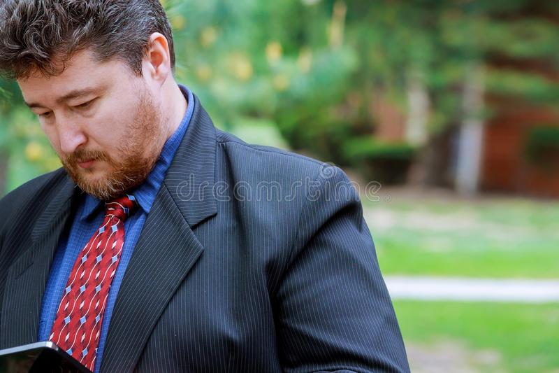 Hombre de negocios moderno del agedn medio confiado en el traje lleno que celebra la tableta digital y la mirada fotografía de archivo