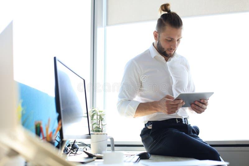 Hombre de negocios moderno joven que trabaja usando la tableta digital mientras que se sienta en la oficina imágenes de archivo libres de regalías