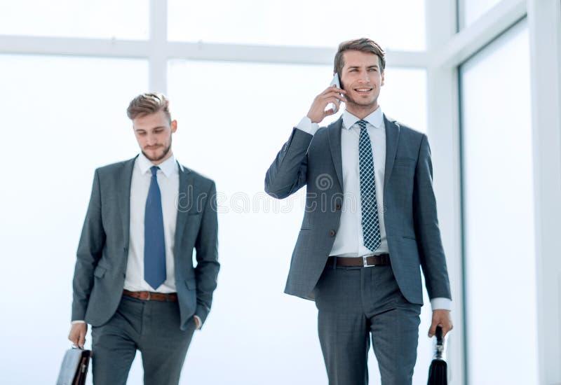 Hombre de negocios moderno que camina abajo de la oficina hal fotos de archivo