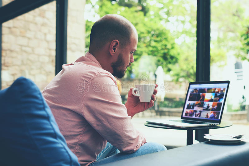Hombre de negocios moderno que conecta con la radio en su ordenador portátil durante descanso para tomar café fotos de archivo libres de regalías
