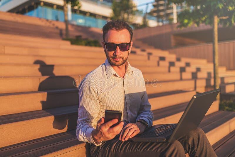 Hombre de negocios moderno que sostiene el teléfono móvil y el ordenador portátil mientras que se sienta en pasos al aire libre fotos de archivo libres de regalías