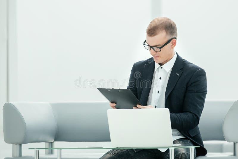 Hombre de negocios moderno que trabaja con los documentos en el pasillo del hotel fotos de archivo libres de regalías