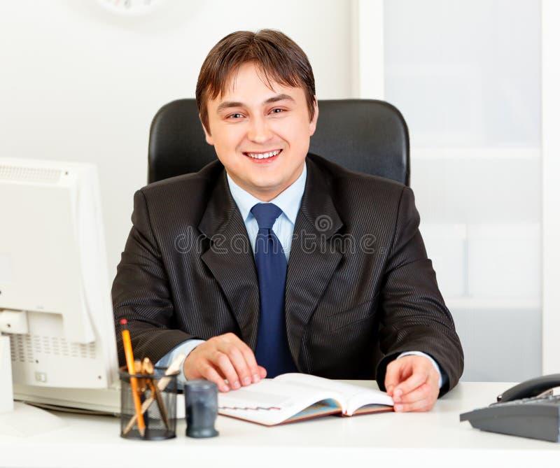 Hombre de negocios moderno sonriente que se sienta en el escritorio de oficina imágenes de archivo libres de regalías