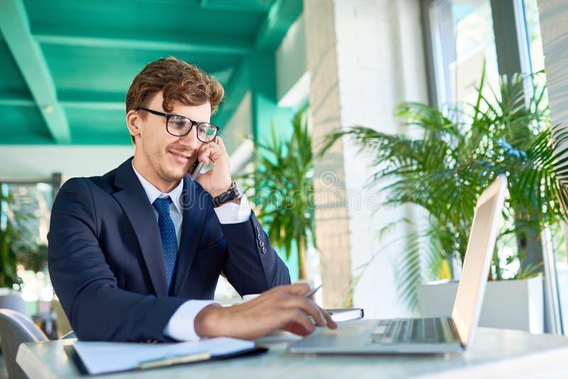 Hombre de negocios moderno Speaking por el teléfono mientras que trabaja foto de archivo