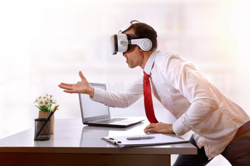 Hombre de negocios muy sorprendido usando los vidrios de la realidad virtual en el suyo fotografía de archivo libre de regalías