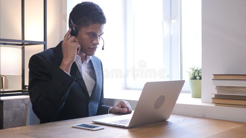 Hombre de negocios negro Attending Customer Call, centro de atención telefónica fotografía de archivo