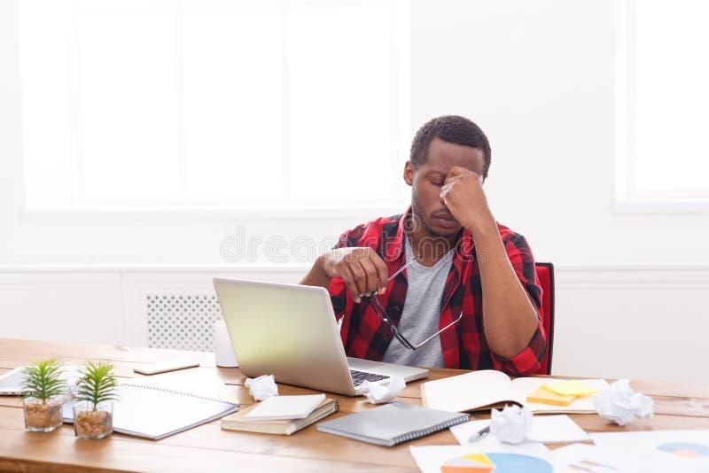 Hombre de negocios negro cansado en la oficina, trabajo con el ordenador portátil imagen de archivo