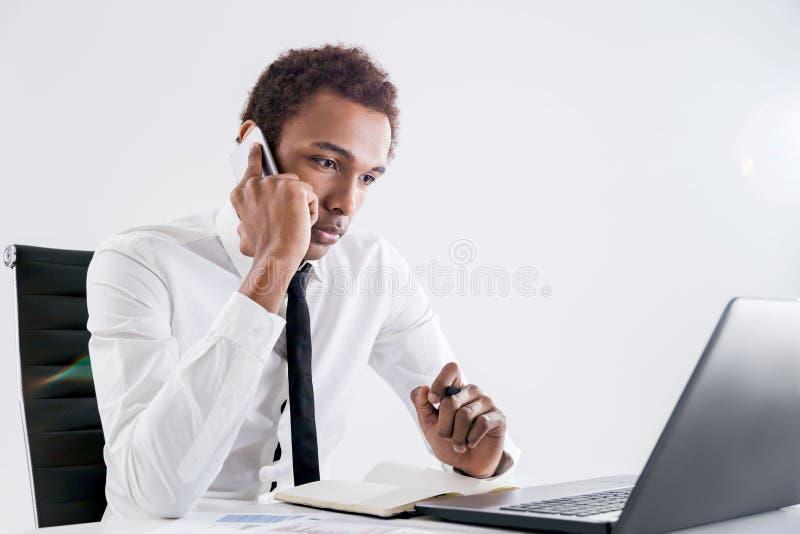 Hombre de negocios negro concentrado en el teléfono fotografía de archivo libre de regalías