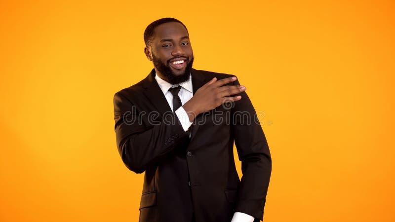 Hombre de negocios negro confiado que sacude el polvo del traje formal, servicios de la limpieza en seco fotografía de archivo