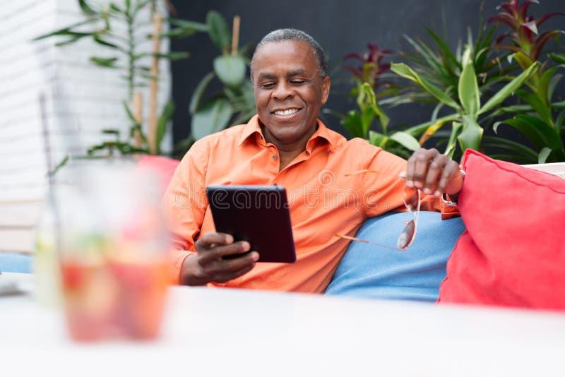 Hombre de negocios negro hermoso usando la tableta imagen de archivo