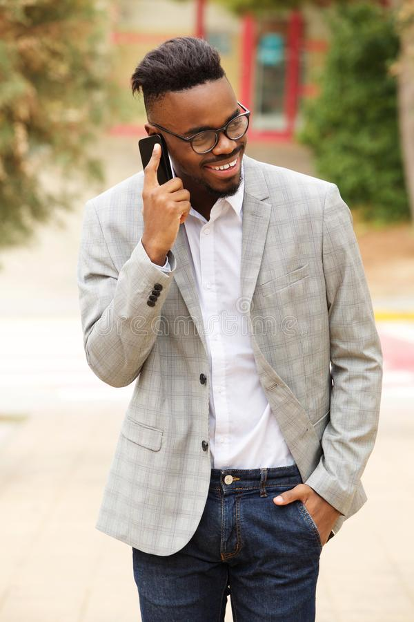 Hombre de negocios negro joven con caminar de los vidrios exterior y hablar en el teléfono móvil imágenes de archivo libres de regalías