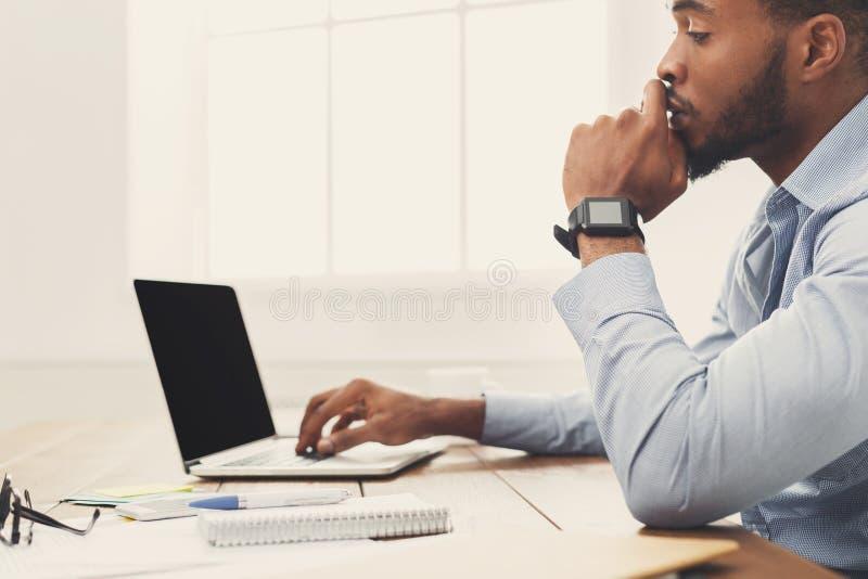 Hombre de negocios negro joven que trabaja con el ordenador portátil fotografía de archivo