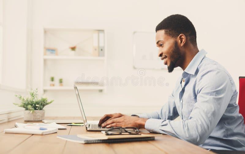 Hombre de negocios negro joven que trabaja con el ordenador portátil imagen de archivo