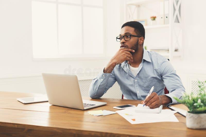 Hombre de negocios negro joven que trabaja con el ordenador portátil imágenes de archivo libres de regalías