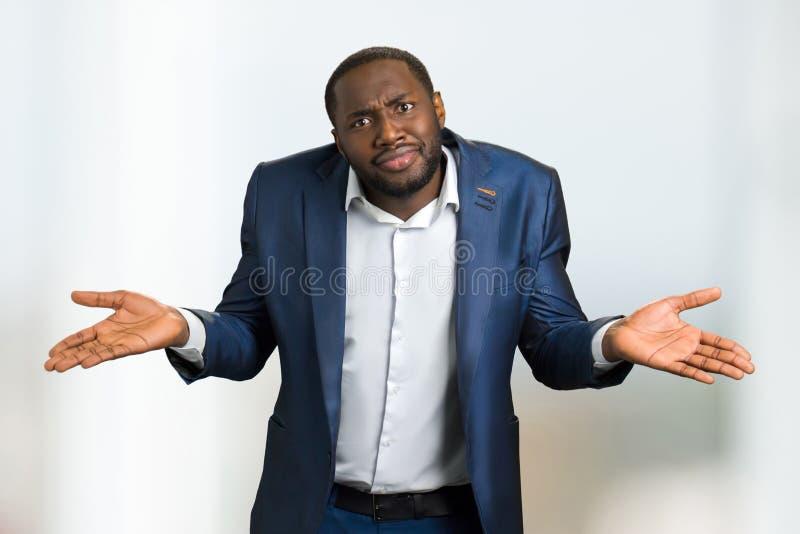Hombre de negocios negro que encoge hombros imagen de archivo