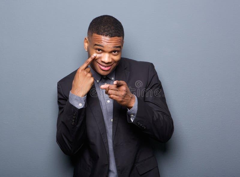 Hombre de negocios negro que señala el finger al ojo fotos de archivo