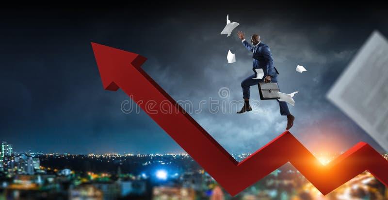 Hombre de negocios negro que sube en la flecha cada vez mayor del zigzag rojo rodeada volando los papeles en un paisaje urbano nu fotos de archivo libres de regalías