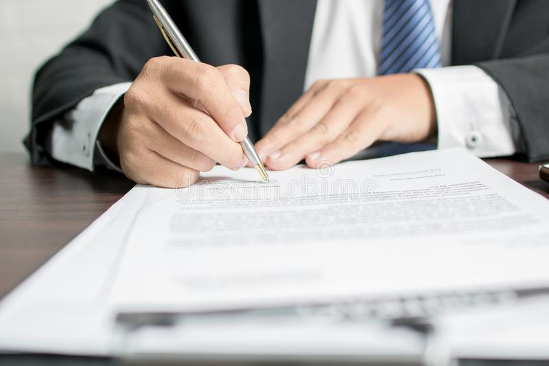 hombre de negocios o abogado que firma en el documento del contrato sobre la tabla en offi fotografía de archivo