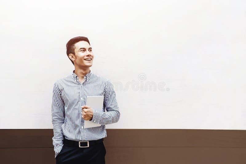 Hombre de negocios o estudiante asiático joven feliz Smiling y llevar a cabo una d foto de archivo libre de regalías