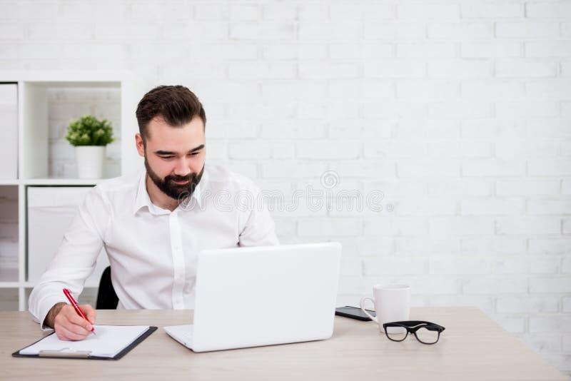 Hombre de negocios o estudiante barbudo alegre que usa el ordenador portátil imagenes de archivo