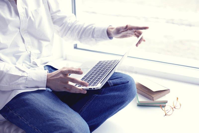Hombre de negocios o estudiante joven que se sienta y que trabaja cerca de ventana con el ordenador portátil abierto en rodillas fotografía de archivo libre de regalías