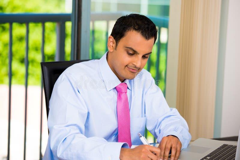 Hombre de negocios o estudiante que trabaja difícilmente en el ordenador portátil y la escritura fotografía de archivo