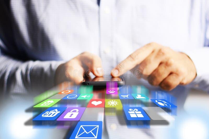 Hombre de negocios o ingeniero que sostiene smartphone con los iconos de los usos que caen fotografía de archivo