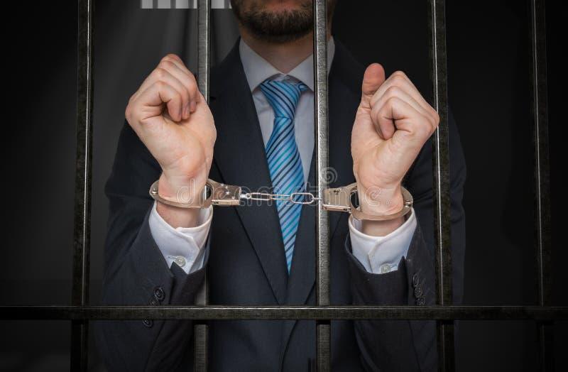 Hombre de negocios o político con las esposas detrás de barras en celda de prisión imagenes de archivo