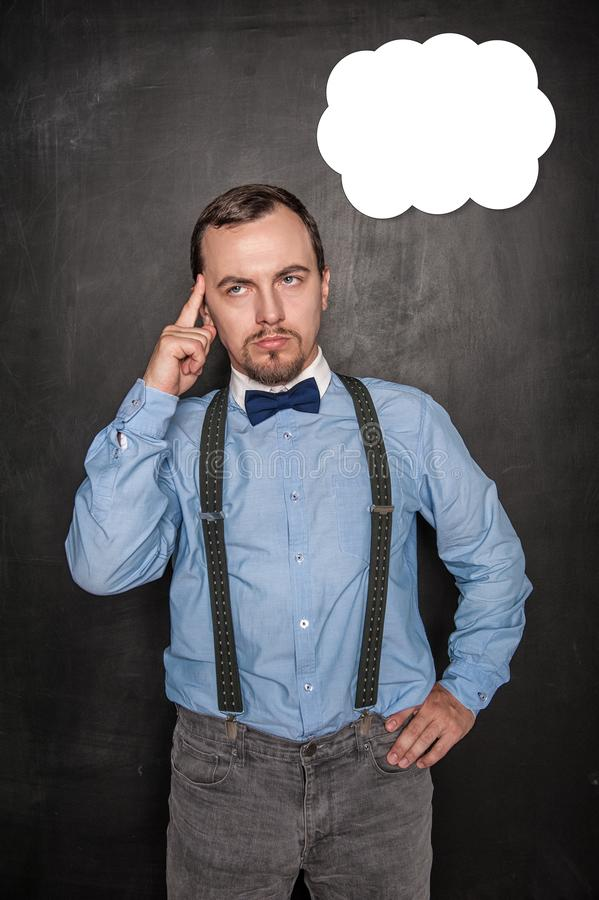 Hombre de negocios o profesor joven pensativo que mira para arriba en la pizarra foto de archivo libre de regalías